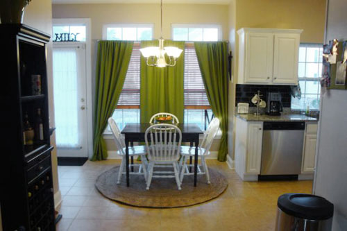 kitchen breakfast nook with rich green curtains on two windows