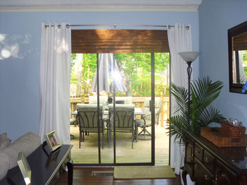 sliding doors treated like window with white curtains on either side and wood blind above