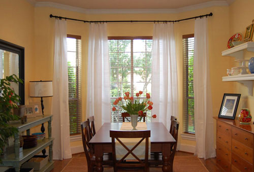 breakfast eating nook in kitchen with long floor to ceiling curtains