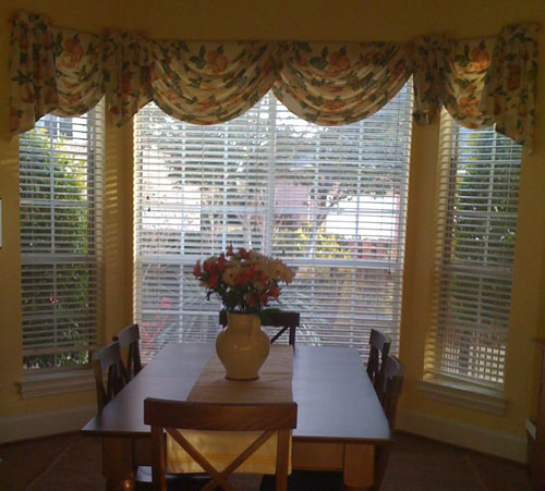 dated bay window in kitchen breakfast nook with floral window valance