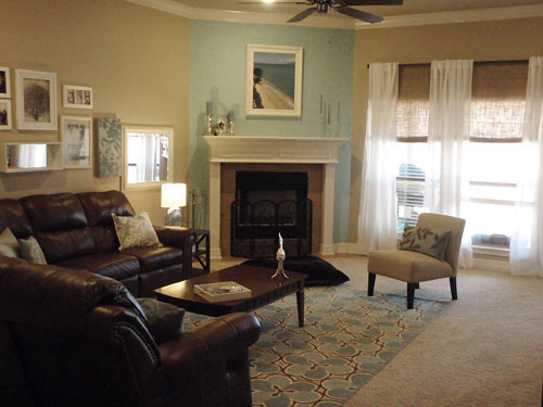 living room with corner fireplace and accent blue wall and white sheer curtains on dark rod
