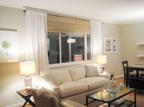 Living room with white sheer curtains hung on oil rubbed bronze