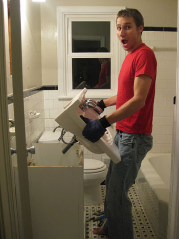 removing an old bathroom sink with your bare hands after plumbing has been detached