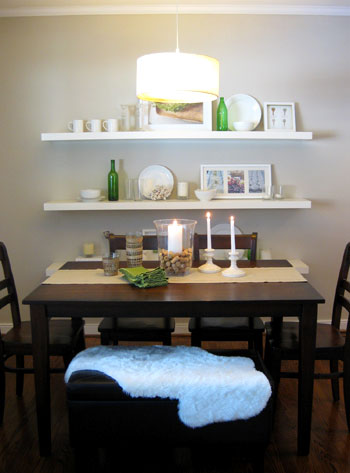 dining room with white floating Ikea shelves and dark wood dining table including bench seat and drum shade pendant