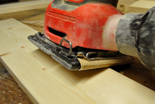using a black & decker palm sander to smooth edges of wood board