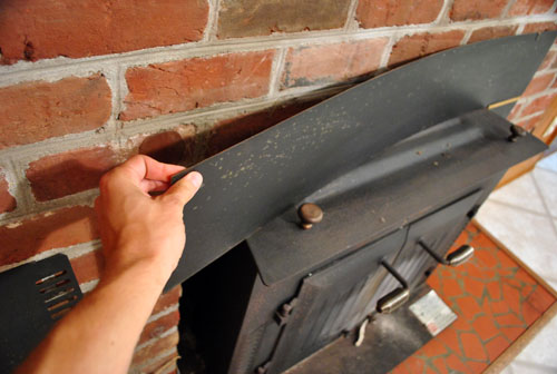 I learned there was only a little bit of glue holding the three pieces  flimsily in place (which made the stove look flush on all sides). - The Beginning Of A Fireplace Makeover: Removing A Woodstove Insert