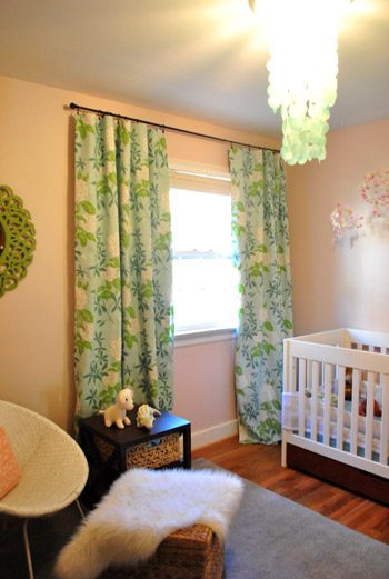 baby girl's pink nursery with colorful blue and green floral curtains featuring a hidden blackout curtains