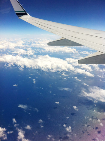 airplane wing over ocean with clouds
