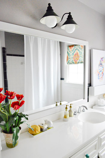 putting a dressed up frame around a plain builder mirror is one of the easiest ways to upgrade a bathroom especially if youre working with the tile and