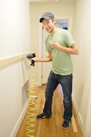 DIYer using Craftmans nail gun to install wood to wall, crossing fingers because its his first time using