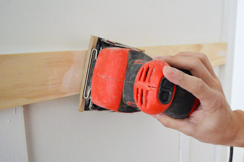 using Black & Decker palm sander to smooth wood filler and spackle in DIY molding installation
