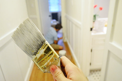 short handle angled paint brush preparing to paint a hallway