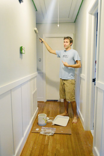 painting a hallway gray with a paint roller using Benjamin Moore Nature Paint in Moonshine color