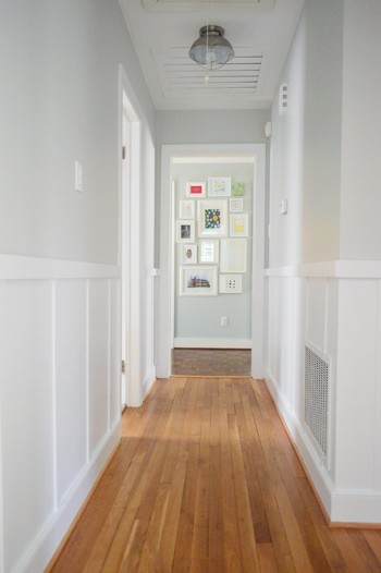gray hallway with white board and batten trim molding looking at picture frame gallery