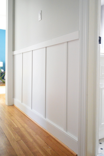 close up of board and batten trim detail in gray hallway with wood floors