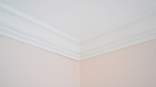Finished ceiling corner with crown molding installed after caulk