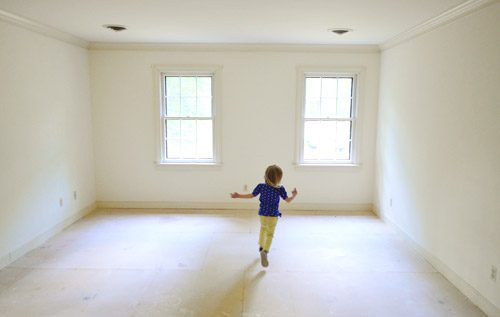 little girl running in empty room with no carpet
