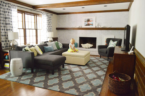 stylish and colorful living room with navy blue furniture, graphic pillows and rug, wood beams, and whitewash brick fireplace wall