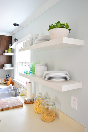 two pairs of white Ikea LACK shelves hung in the kitchen with white plates, bowls, and colorful cups