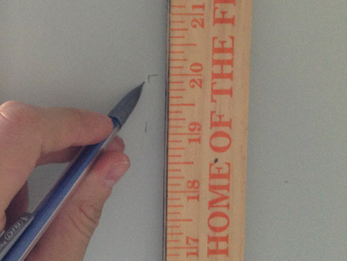 using a yardstick and pencil to mark the height and placement of kitchen floating shelves