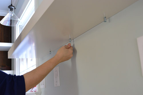 securing Ikea LACK shelf into place on metal hanging bracket using screws on the underside