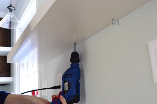 using powerdrill to screw Ikea floating shelf to secure it to wall bracket