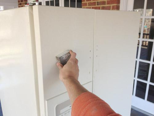 sanding fridge in preparation for paint