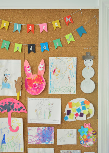 close up detail of kids art hung on cork board wall including name banner bunting from etsy