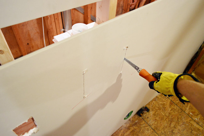 using drywall saw to cut hole for laundry plumbing in drywall sheet