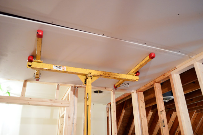 sheetrock panel held against ceiling of laundry room using drywall lift