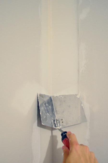 dragging corner trowel down corner of drywalled wall
