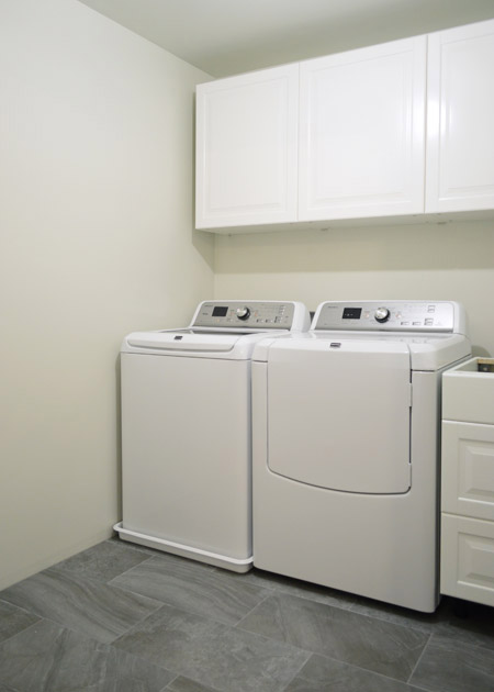 washing machine and drain pan, next to a dryer