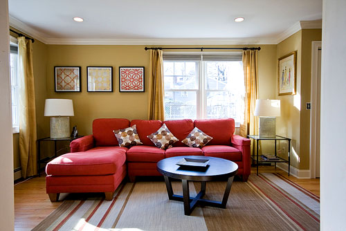 bright red sofa sectional in living room with neutral accents