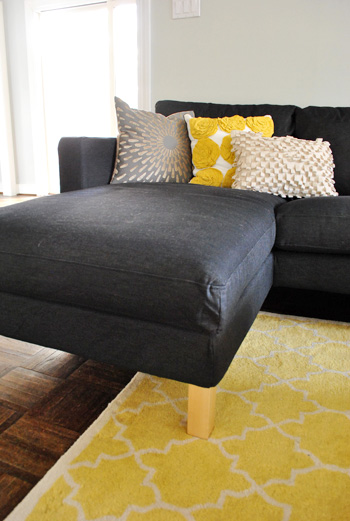 chaise portion of ikea sectional sofa in dark sivik gray with yellow accents