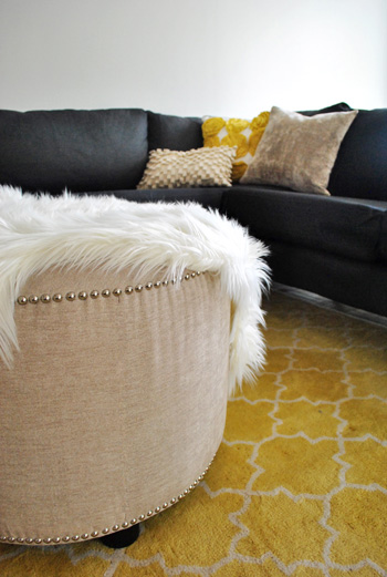 large round upholstered ottoman with nail head trim atop yellow pottery barn rug