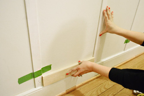 using wood block to space vertical boards evenly across hallway wall in board & batten molding installation