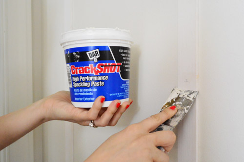 applying DAP CrackShot High Performance Spackling Paste to fill nail holes in wood DIY project