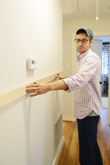 DIYer holding up wood board in hallway to determine height of board & batten project
