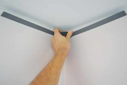 John measuring corner of ceiling wall with angle finder tool