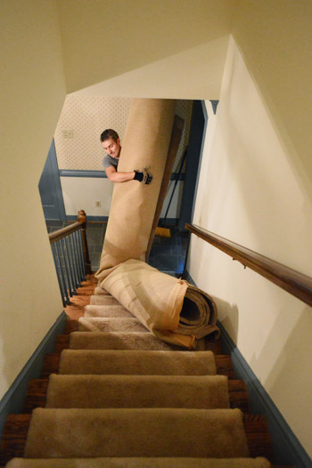 hauling old carpet roll down stairs