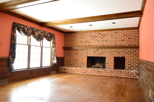 dated 1980s living room with dark brick wall, wood beams, and red salmon colored walls