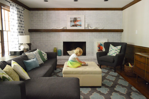 living room with navy blue furniture and a whitewash brick fireplace wall