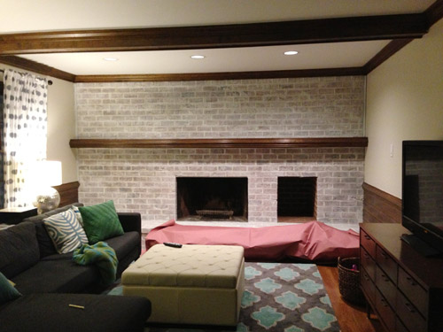 lightly whitewashed brick wall in living room with fireplace and mantle using leftover white paint