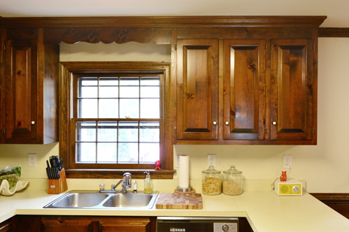 before photo of dated 1980s kitchen with dark wood wall cabinets