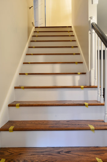 taping off placement of stair runner on wooden staircase