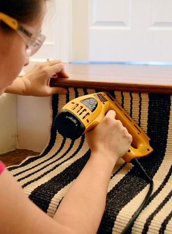 Sherry using electric staple gun to apply stapes to black and white runner under first tread