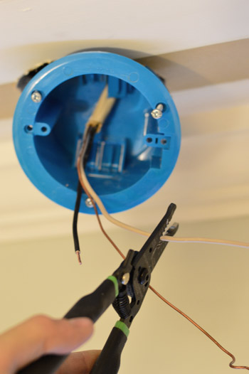 Stripping wires from old fluorescent light fixture while installing new old work box