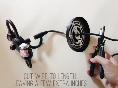 Hand cutting wires on dark pendant light fixture cord
