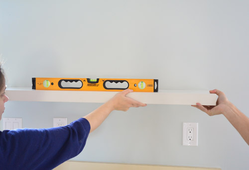 using a level to mark placement of Ikea floating shelves on kitchen wall