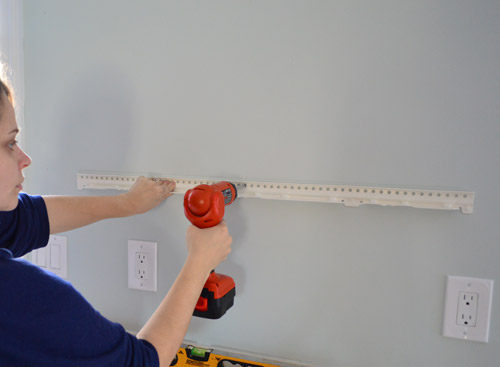 attaching metal hanging bracket for Ikea floating shelf using a drill driver to screw it to kitchen wall